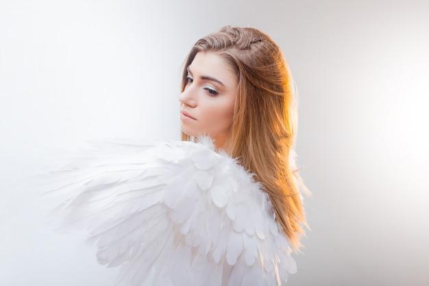 Jovem loira maravilhosa à imagem de um anjo com asas brancas.