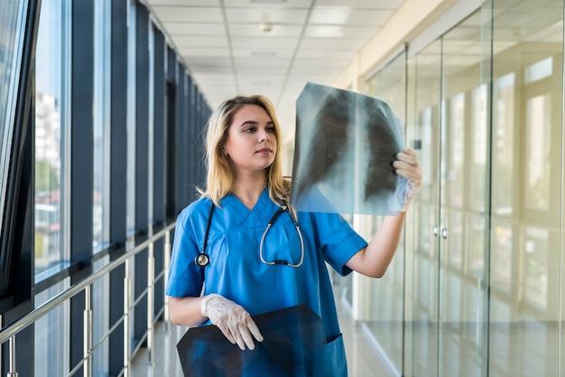 Jovem loira médica vestindo uniforme azul com estetoscópio segurando um filme de raio x de tórax e verificando pneumonia. covid19