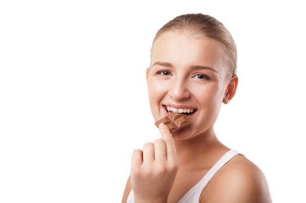 Jovem loira mordendo chocolate isolado