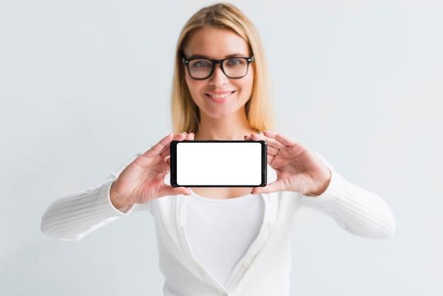Jovem loira mostrando a tela do smartphone