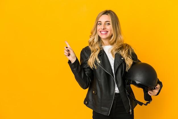 Jovem loira motoqueira segurando capacete sorrindo e apontando para o lado, mostrando algo no espaço em branco