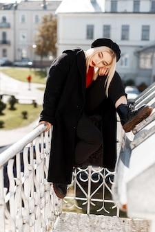 Jovem loira muito elegante com um casaco elegante com botas e uma boina preta da moda com lábios vermelhos posando sentada em uma varanda vintage em um dia ensolarado