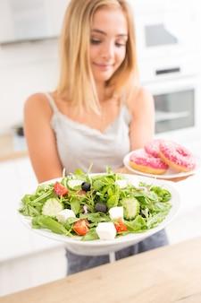 Jovem loira no café da manhã ou jantar na cozinha de casa escolhe entre donut e salada de legumes.