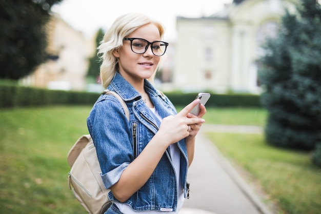 Jovem loira ocupada usa o telefone para rolar conversa em rede social na cidade, outono quadrado manhã