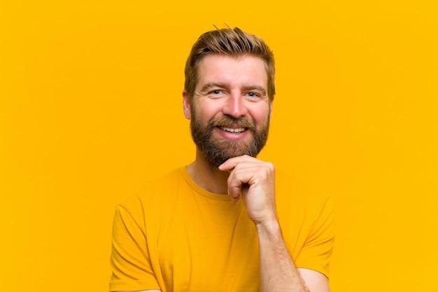 Jovem loira olhando feliz e sorrindo com a mão no queixo, pensando em fazer uma pergunta, comparando a parede de opções laranja