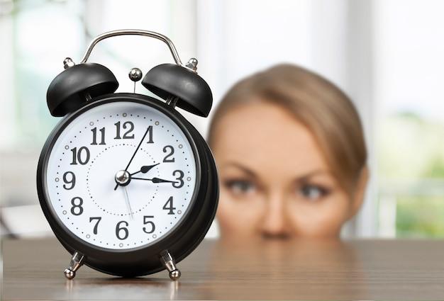 Jovem loira olhando para um despertador vintage preto
