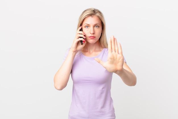 Jovem loira olhando séria, mostrando a palma da mão aberta fazendo gesto de pare e ligando com um telefone inteligente