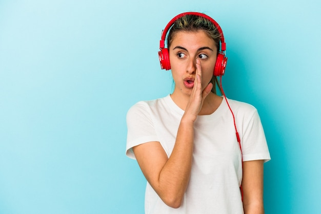 Jovem loira ouvindo música em fones de ouvido isolados em um fundo azul está contando uma notícia secreta de travagem e olhando para o lado