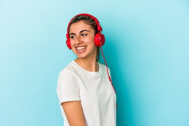 Jovem loira ouvindo música em fones de ouvido isolados em um fundo azul parece de lado sorrindo, alegre e agradável.