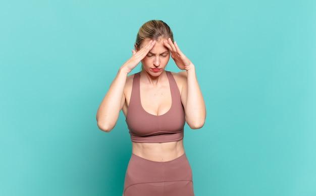Jovem loira parecendo estressada e frustrada, trabalhando sob pressão, com dor de cabeça e preocupada com problemas. conceito de esporte
