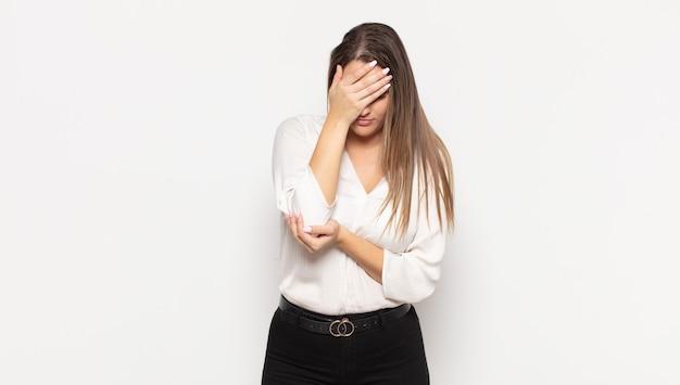 Jovem loira parecendo estressada, envergonhada ou chateada, com dor de cabeça, cobrindo o rosto com a mão