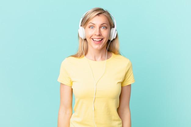 Jovem loira parecendo feliz e agradavelmente surpresa e ouvindo música.