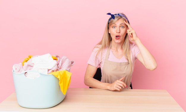 Jovem loira parecendo feliz, espantada e surpresa. conceito de lavar roupas