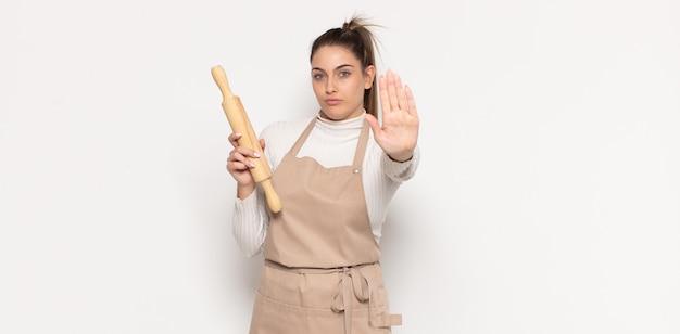 Jovem loira parecendo séria, severa, descontente e irritada, mostrando a palma da mão aberta fazendo gesto de pare