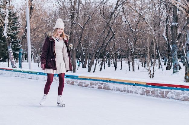 Jovem loira patinando no parque de inverno nevado.