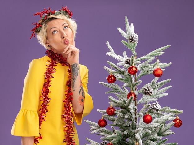 Jovem loira pensativa com coroa de flores de natal e guirlanda de ouropel no pescoço, em pé perto da árvore de natal decorada, segurando o queixo franzindo os lábios olhando para cima, isolado na parede roxa