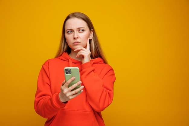 Jovem loira pensativa mantendo a mão no queixo, segurando e olhando para o celular