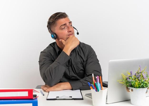 Jovem loira pensativa, trabalhador de escritório com fones de ouvido, sentada na mesa com ferramentas de escritório, usando laptop coloca a mão no queixo olhando para o lado