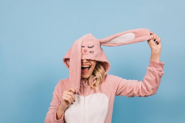 Jovem loira posando com fantasia de coelho rosa