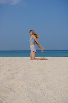 Jovem loira pratica ioga e meditação e se divertindo na praia em um dia ensolarado.