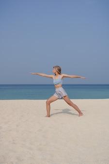 Jovem loira pratica ioga e meditação na pose de preocupador ou virabhadrasana asana na praia em um dia ensolarado.