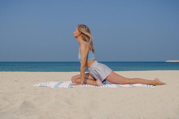 Jovem loira praticando ioga e meditação no asana one legged king pigeon pose single pigeon asana na praia em um dia ensolarado