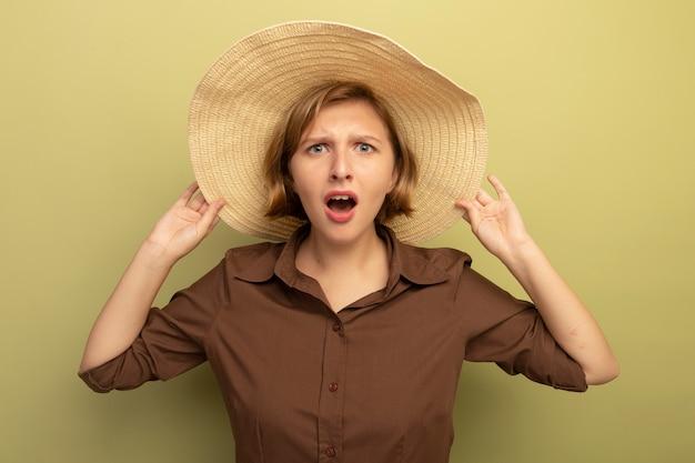Jovem loira preocupada com chapéu de praia agarrado