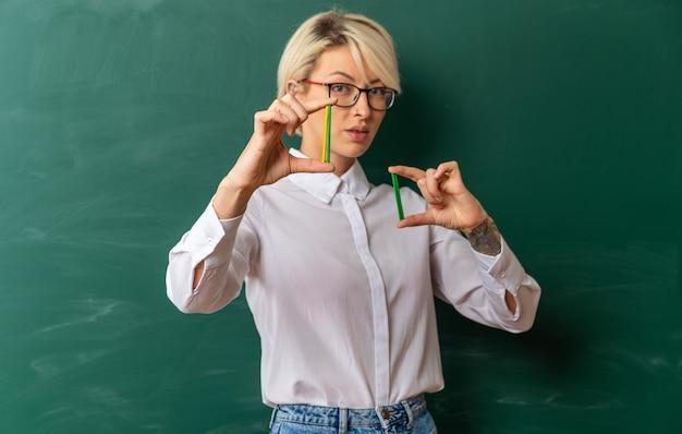 Jovem loira professora confiante usando óculos na sala de aula em frente ao quadro-negro, mostrando a contagem de paus olhando para a câmera