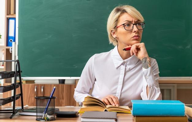 Jovem loira professora rígida usando óculos, sentada na mesa com ferramentas escolares na sala de aula, segurando um livro aberto e segurando a caneta sob o queixo