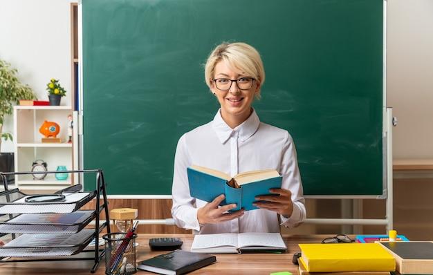 Jovem loira professora sorridente de óculos, sentada na mesa com o material escolar na sala de aula, segurando um livro aberto, olhando para a frente
