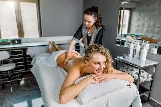 Jovem loira relaxada recebendo massagem nas costas manual clássica no interior moderno spa ou sala de massagem. massagista feminina jovem fazendo massagem no corpo da mulher no salão spa médico