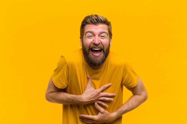 Jovem loira rindo alto em alguma piada hilariante, sentindo-se feliz e alegre, se divertindo na parede laranja