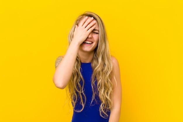 Jovem loira rindo e dando um tapa na testa como dizer 'oh! eu esqueci ou isso foi um erro estúpido contra parede amarela
