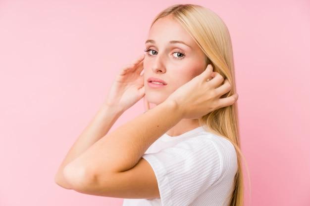 Jovem loira rosto closeup isolado em uma parede rosa
