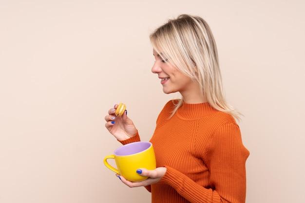 Jovem loira russa segurando macarons franceses coloridos e um copo de leite