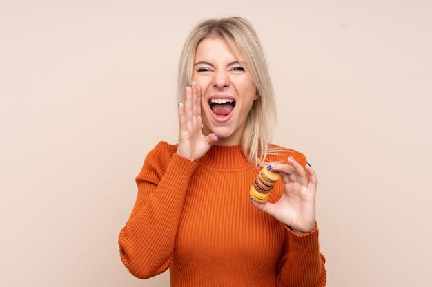Jovem loira russa sobre parede isolada segurando macarons franceses coloridos e gritando