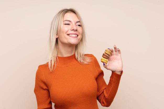 Jovem loira russa sobre parede isolada segurando macarons franceses coloridos e olhando para cima enquanto sorrindo