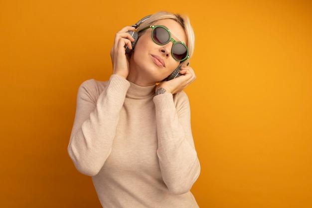 Jovem loira satisfeita usando óculos escuros e fones de ouvido segurando fones de ouvido e ouvindo música