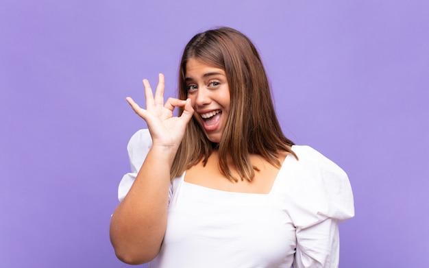 Jovem loira se sentindo bem-sucedida e satisfeita, sorrindo com a boca bem aberta, fazendo sinal de ok com a mão