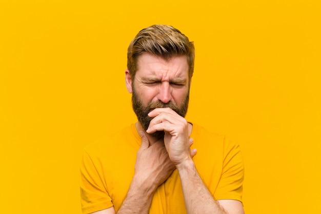 Jovem loira se sentindo doente com dor de garganta e sintomas de gripe, tosse com a boca coberta