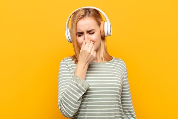 Jovem loira se sentindo enojada, segurando o nariz para evitar cheirar um fedor desagradável