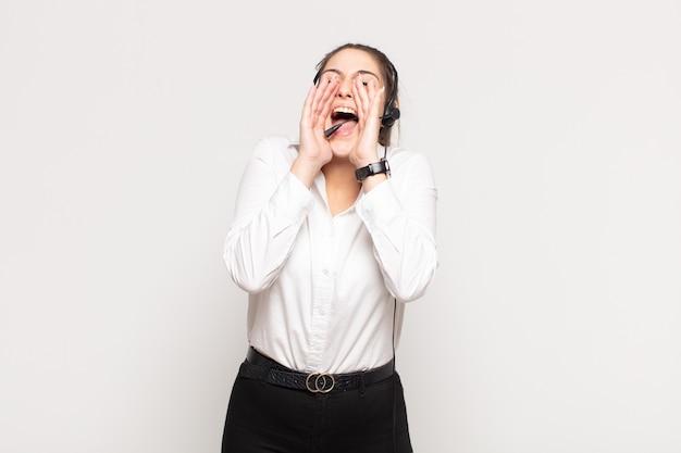 Jovem loira se sentindo feliz, animada e positiva, dando um grande grito com as mãos perto da boca