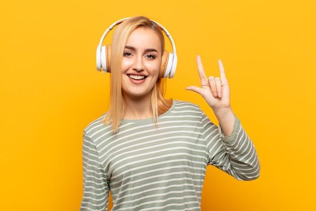 Jovem loira se sentindo feliz, divertida, confiante, positiva e rebelde, fazendo sinal de rock ou heavy metal com a mão