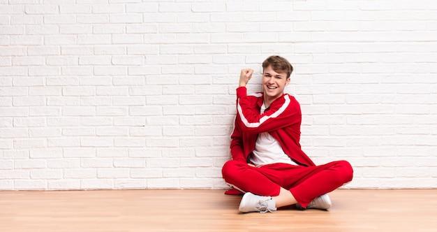Jovem loira se sentindo feliz, satisfeito e poderoso, flexionando o ajuste e o bíceps muscular, parecendo forte após a academia, sentada no chão
