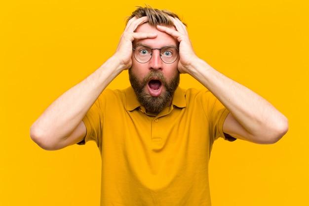 Jovem loira se sentindo horrorizado e chocado, levantando as mãos à cabeça e entrando em pânico por um erro contra a parede laranja