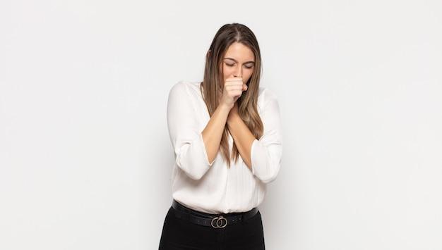 Jovem loira se sentindo mal, com dor de garganta e sintomas de gripe, tosse com a boca coberta