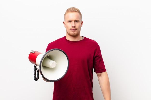 Jovem loira se sentindo triste, chateado ou com raiva e olhando para o lado com uma atitude negativa, franzindo a testa em desacordo contra a parede branca com um megafone