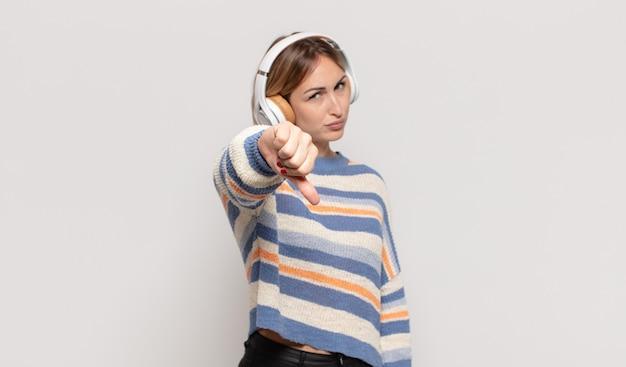 Jovem loira se sentindo zangada, irritada, irritada, decepcionada ou descontente, mostrando o polegar para baixo com um olhar sério