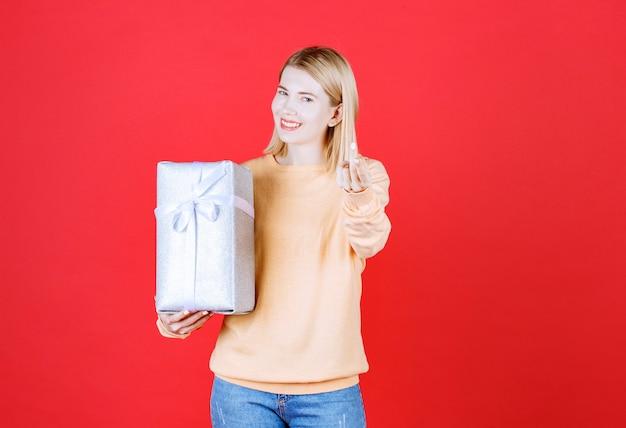 Jovem loira segurando a caixa de presente do lado direito enquanto faz um sinal com a mão na frente da parede vermelha
