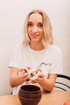 Jovem loira segurando cogumelos picados nas mãos e sorrindo